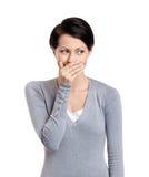 La donna ride scioccamente copertura la sua bocca Fotografia Stock