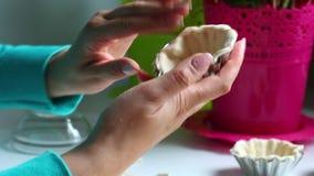 La donna riempie la pasta di piatto di cottura Preme la pasta nella muffa con le vostre dita Accanto alla tavola è il resti video d archivio