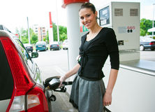 La donna rifornisce di carburante la sua automobile Fotografia Stock