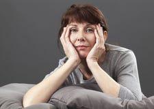 La donna rilassata felice 50s ha messo sui cuscini grigi Immagine Stock