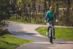 La donna rilassata sta esplorando il parco sulla bicicletta fotografia stock