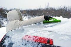 La donna rimuove la neve dal tetto dell'automobile Immagini Stock Libere da Diritti