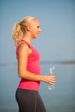 La donna riposa dopo l'allenamento di mattina sulla spiaggia Fotografie Stock Libere da Diritti