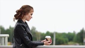 La donna romantica in un bomber e con un caffè in sue mani distoglie lo sguardo video d archivio