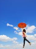 La donna rossa dell'ombrello salta al cielo Fotografie Stock