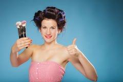 La donna in rulli dei capelli tiene le spazzole di trucco Fotografie Stock Libere da Diritti