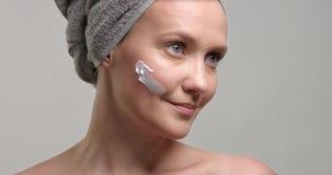 la donna 30s mette una crema sulla guancia video d archivio