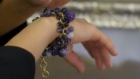 La donna s separa a mano fuori le gemme sul braccialetto dei gioielli stock footage