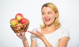 La donna sa soggiorno nella forma ed è in buona salute Approfitti di questi prodotti e morso di caduta nella mela succosa tenuta  fotografia stock libera da diritti