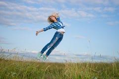 La donna salta nel campo di erba verde Fotografia Stock