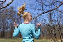 La donna salta nel legno in anticipo della molla Immagini Stock