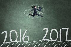La donna salta sulla lavagna verso 2017 Fotografia Stock Libera da Diritti