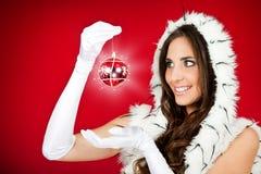 La donna in Santa copre la sfera lucida di natale della holding Immagine Stock