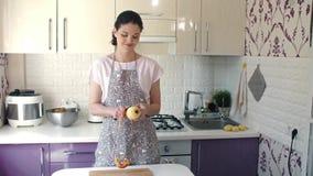 La donna sbuccia una mela alla cucina archivi video