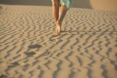 La donna scalza cammina nella sabbia del deserto Fotografia Stock Libera da Diritti