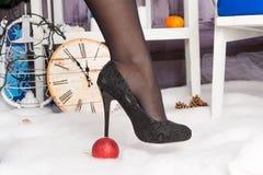 La donna in scarpe nere è venuto sul tallone della decorazione per l'albero di Natale sotto forma di ciotola di vetro rossa Immagini Stock
