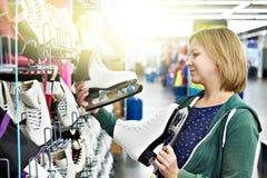 La donna sceglie la figura pattini nel negozio di sport immagine stock libera da diritti