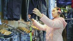 La donna sceglie i pantaloni nel deposito stock footage