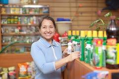 La donna sceglie i prodotti chimici agricoli nella memoria fotografia stock