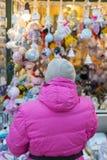 la donna sceglie i ricordi al mercato di Natale Vista posteriore Foto verticale fotografie stock libere da diritti