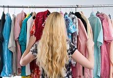 La donna sceglie i vestiti nel gabinetto del guardaroba immagini stock libere da diritti
