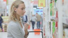 La donna sceglie il succo nel supermercato archivi video