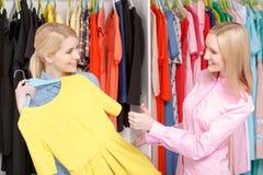 La donna sceglie il vestito in un deposito immagini stock