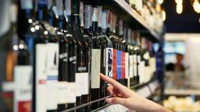 La donna sceglie il vino nel supermercato, cliente seleziona il prodotto sugli scaffali nel deposito in primo piano stock footage
