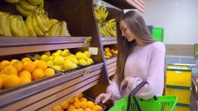 La donna sceglie le arance ad un supermercato archivi video