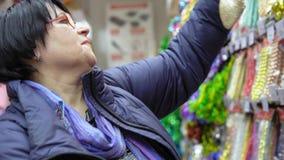 La donna sceglie le decorazioni di festa di Natale nel centro commerciale stock footage