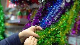 La donna sceglie le decorazioni di festa di Natale nel centro commerciale video d archivio