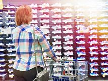 La donna sceglie le scarpe da tennis nel negozio di vestiti di sport fotografie stock libere da diritti