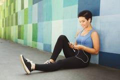 La donna sceglie la musica per ascoltare durante l'allenamento Immagine Stock Libera da Diritti