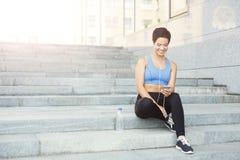 La donna sceglie la musica per ascoltare durante l'allenamento Immagine Stock
