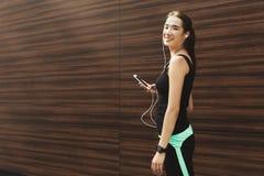 La donna sceglie la musica per ascoltare durante l'allenamento Fotografia Stock