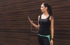 La donna sceglie la musica per ascoltare durante l'allenamento Fotografia Stock Libera da Diritti