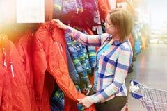 La donna sceglie la tuta dello sci nel deposito di sport immagini stock