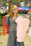 La donna sceglie una camicetta immagini stock