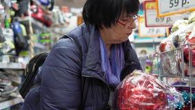 La donna sceglie una grande palla per un albero di Natale nel centro commerciale stock footage