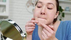 La donna schiaccia l'acne Guardando nello specchio nella cucina video d archivio