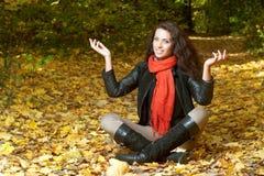 La donna in sciarpa rossa si siede a gambe accavallate e sollevando le sue mani Fotografia Stock Libera da Diritti