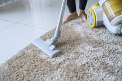 La donna sconosciuta pulisce il tappeto con un aspirapolvere fotografia stock