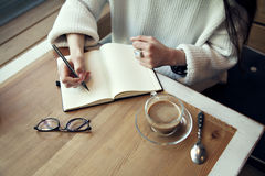 La donna scrive nella vista del blocco note da sopra dentro un ristorante vicino a tempo del pranzo della finestra con caffè Fotografia Stock
