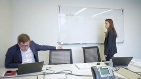 La donna scrive sul bordo magnetico, parlante con uomo nella grande società stock footage