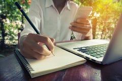 La donna scrive sul telefono cellulare della tenuta e del taccuino con il tono dell'annata del computer portatile Immagine Stock Libera da Diritti