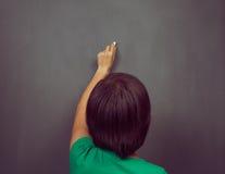La donna scrive sulla lavagna Fotografia Stock Libera da Diritti