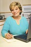 La donna scrive una nota mentre per mezzo di un computer portatile. Immagini Stock Libere da Diritti