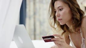 La donna seducente si è vestita nelle bugie degli indumenti da notte sul letto e sul usando il suoi computer portatile e carta di stock footage