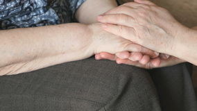 La donna segna la mano di una donna corrugata anziana stock footage