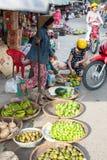 La donna seleziona le arance al mercato bagnato fotografia stock